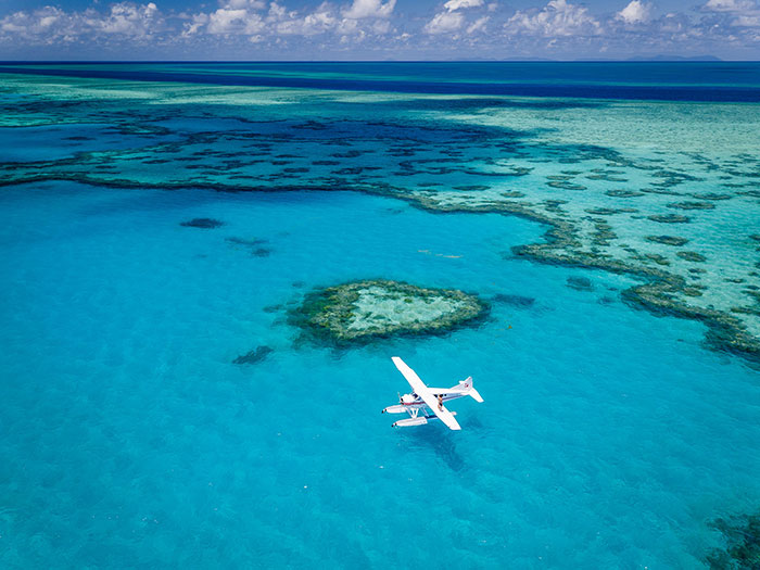 Sea plane flying over heart reef