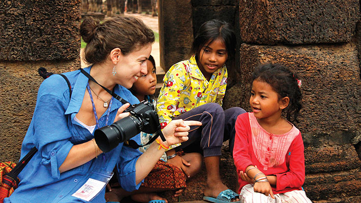 Tourist with local children in Cambodia