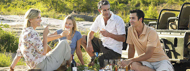 Group of people eating a picnic while on safari