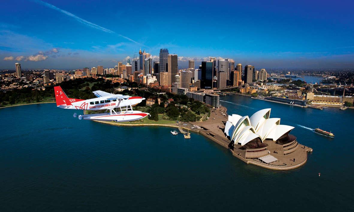 A seaplane flying over Sydney Opera House