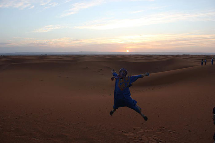 Anna jumping in the desert, Morocco