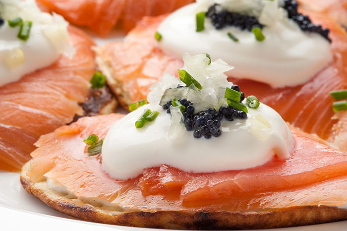 Blini topped with smoked salmon, sour cream and caviar