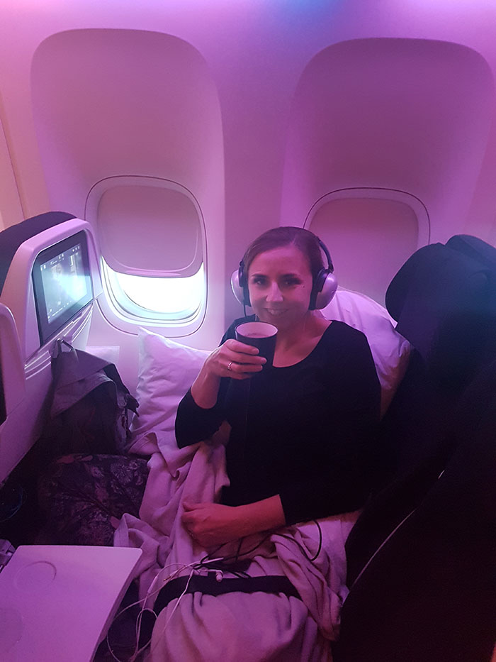 Me enjoying tea and a movie on the Air New Zealand Economy Skycouch