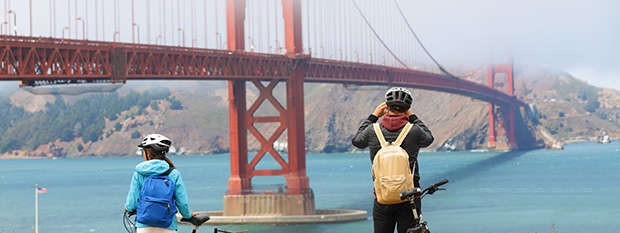 Couple on bikes overlooking the Golden Gate Bridge