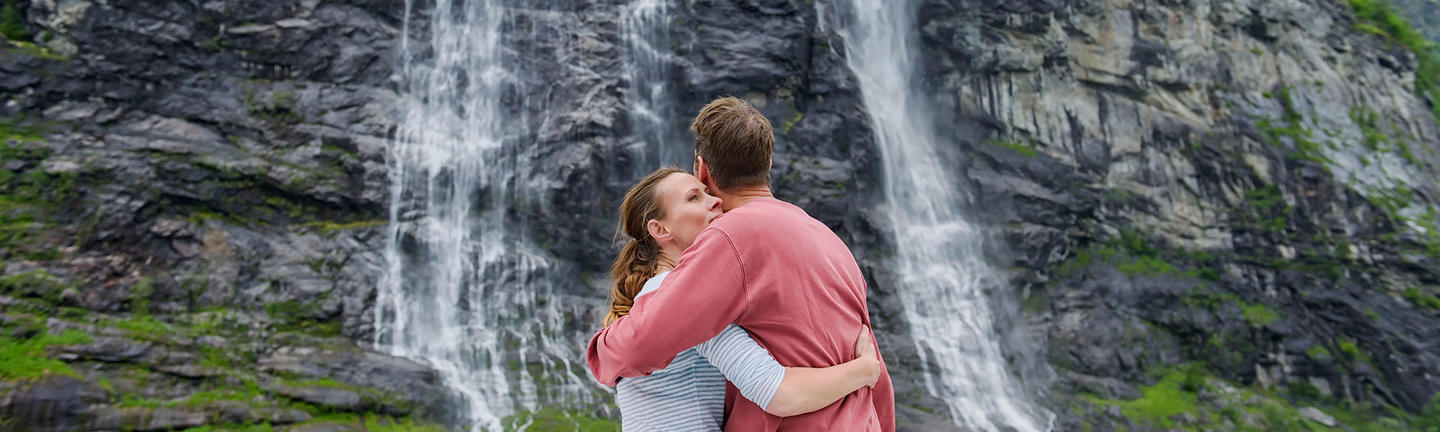 Couple viewing waterfalls onboard a Hurtigruten cruise