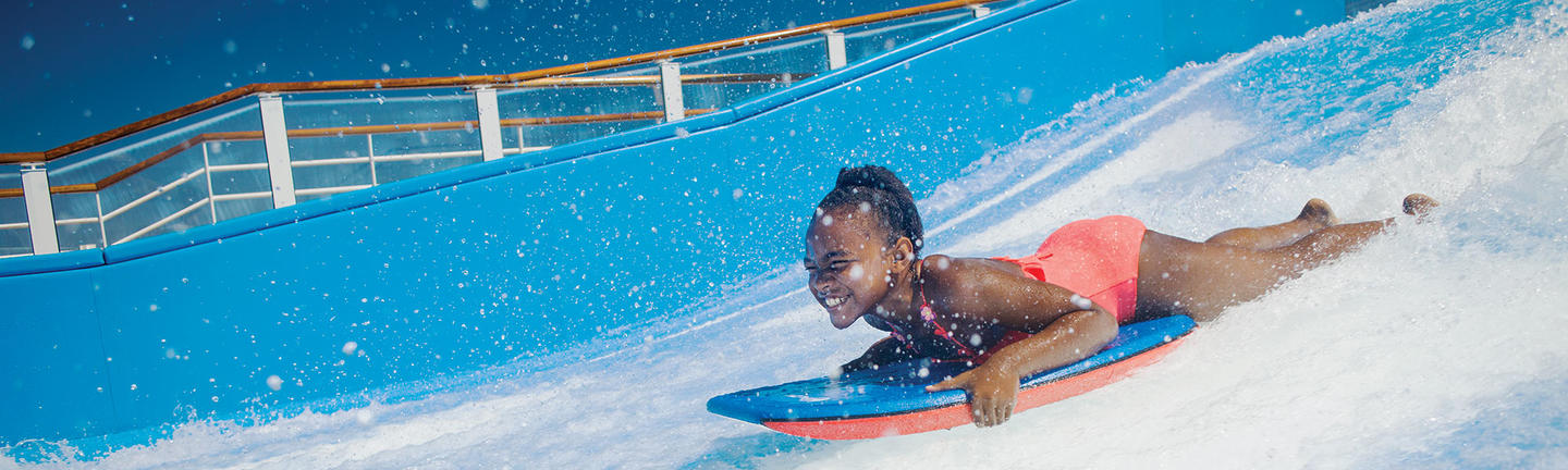 Young girl surfing on the Florider onboard Royal Caribbean