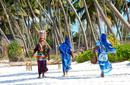 Local women walking along a beach, Zanzibar