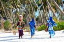 Local women walking along a beach, Zanzibar