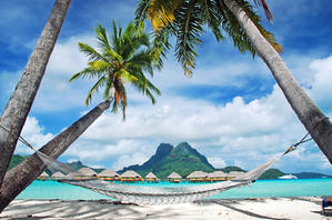 Hammock overlooking a lagoon with overwater bungalows