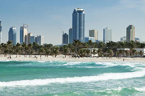 Waves on the beach with Dubai city buildings in the background