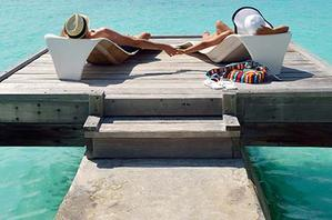 Couple lying on a jetty in the Maldives