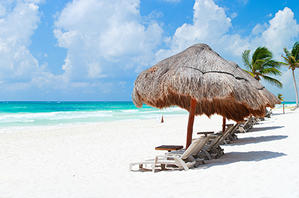 White sandy beach with lounges in Tulum