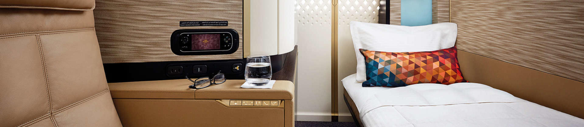 A flat bed and seat inside a Etihad First Apartment