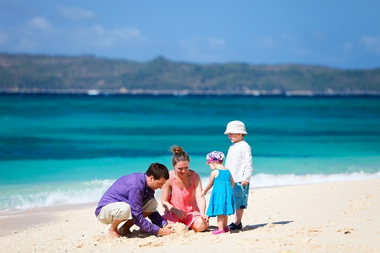 Family of four building sand castle on tropical beach