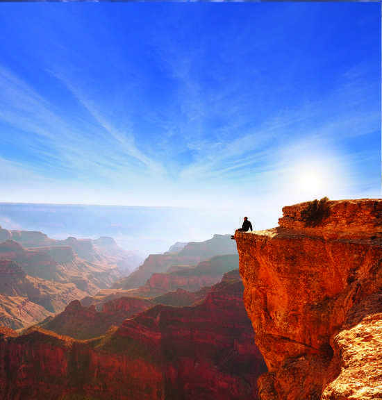 Man on Ledge Against Blue Sky at Grand Canyon