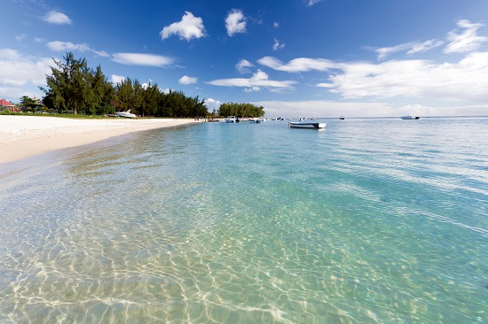 View along Flic en Flac Beach showing the clear shallows of the Indian Ocean, blue sky and white sand, on the west coast of Mauritius, Indian Ocean, Africa