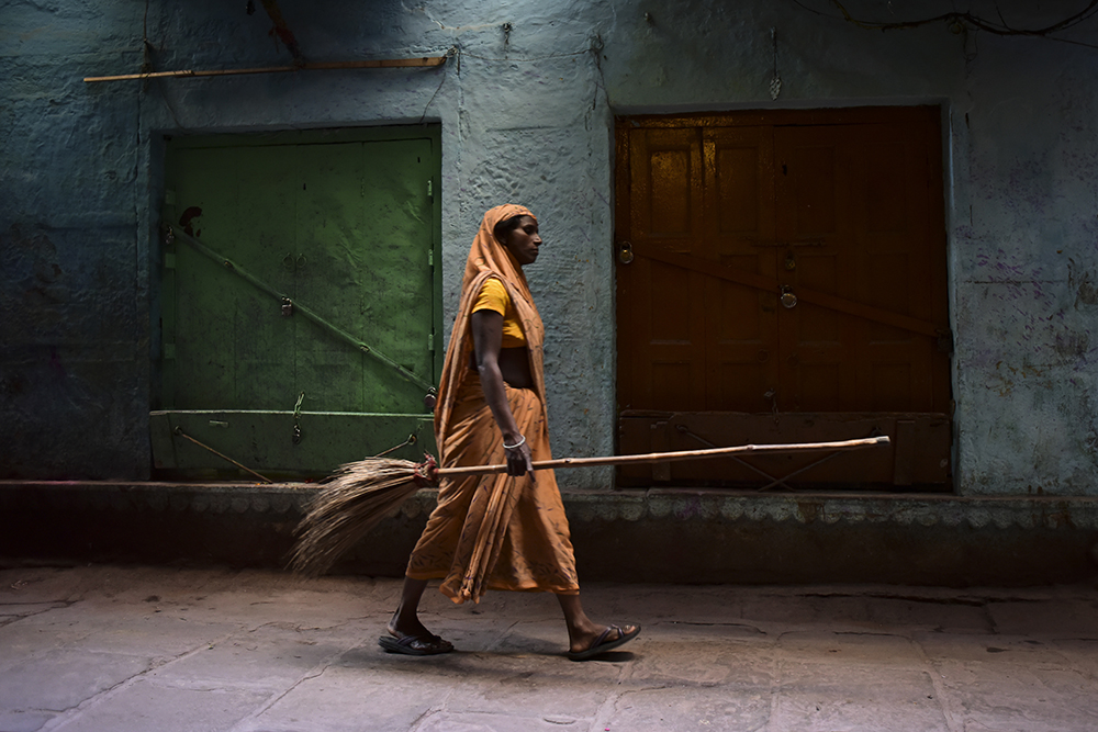 Woman walking the streets with a broom in India