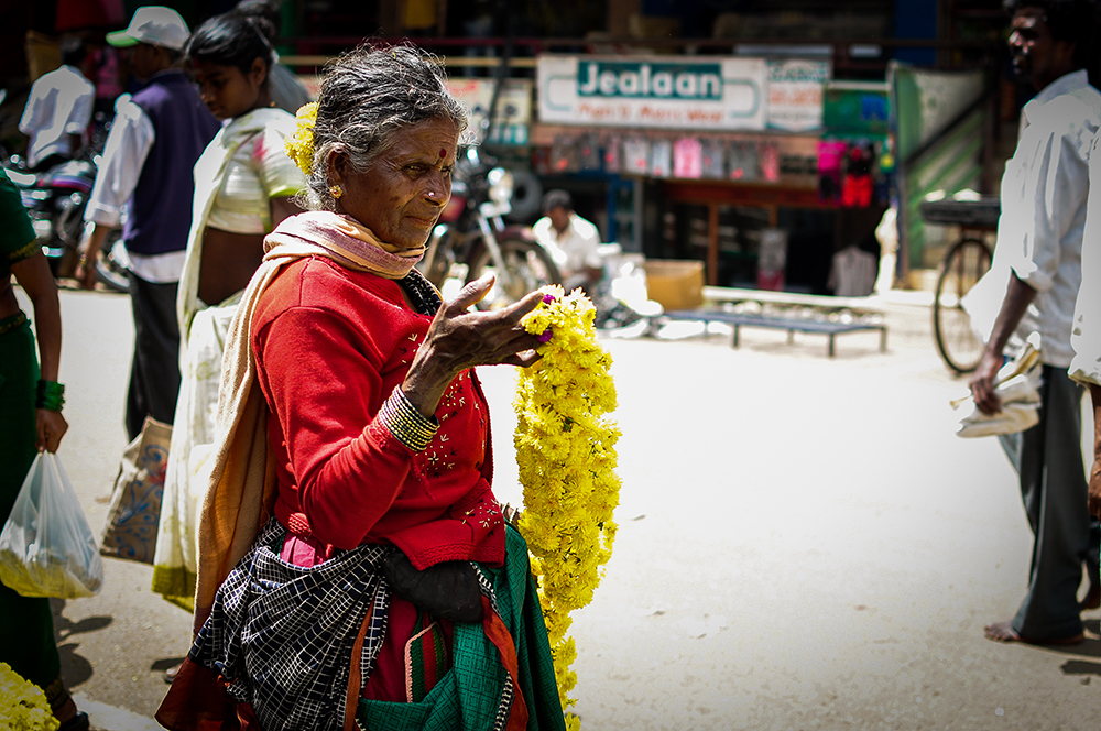 Old woman holding yellow flowers on the street of Hunsur