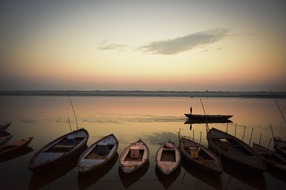 Boats on the water at sunrise on the River Ganges