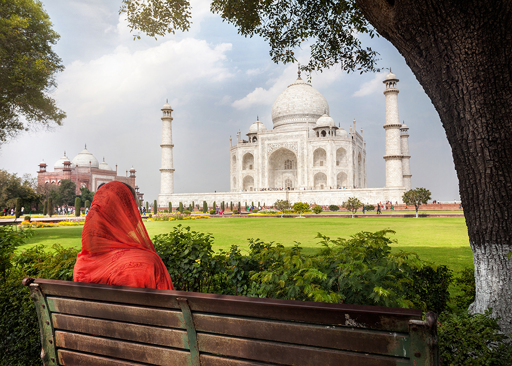 Woman in red scarf sitting on the bench in the shadow and looking at Taj Mahal in Agra, Uttar Pradesh, India-RS