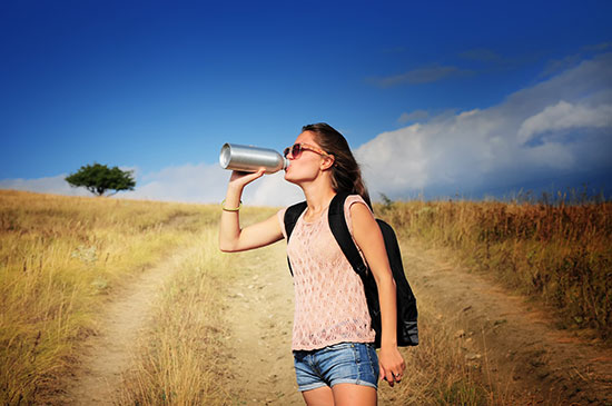 Woman drinking water from water bottle in a field
