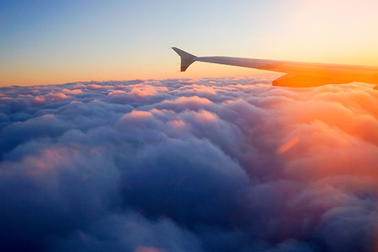 A plane wing above the clouds at sunrise