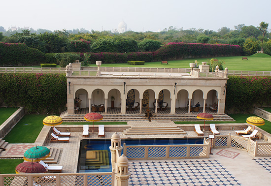 The lucurious pool area at the Oberoi Amarvilas in Agra with the Taj Mahal in the background.