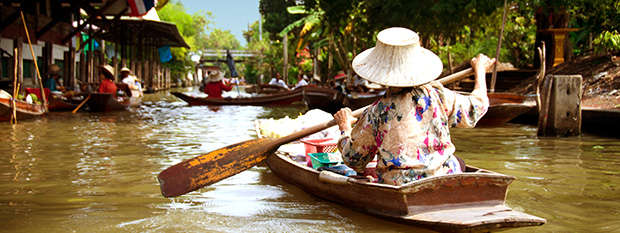 Woman paddling through a floating market