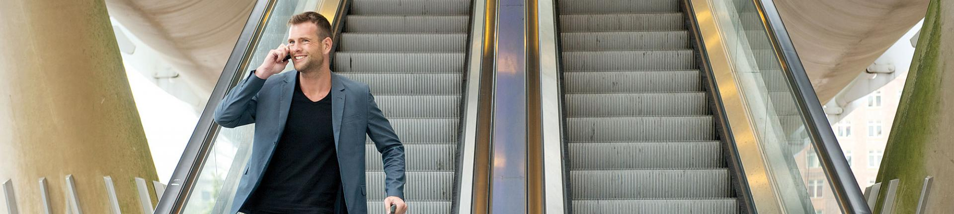 Man on phone standing on escalator